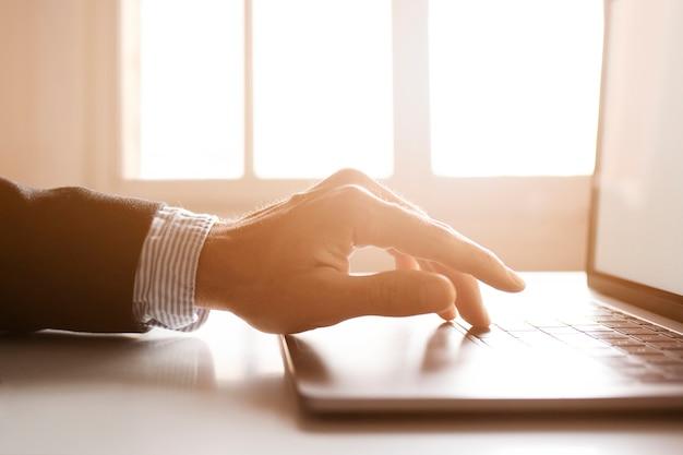 Mãos de um empresário usando laptop na internet