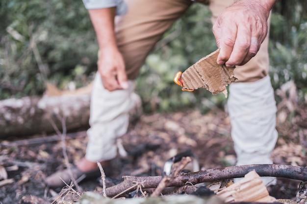 Mãos de um fazendeiro local fazendo uma fogueira.