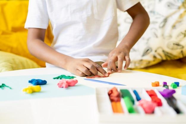 Mãos de um garoto africano ou mestiço do ensino fundamental ou pré-escolar achatando um pedaço de plasticina na mesa enquanto desenham no papel