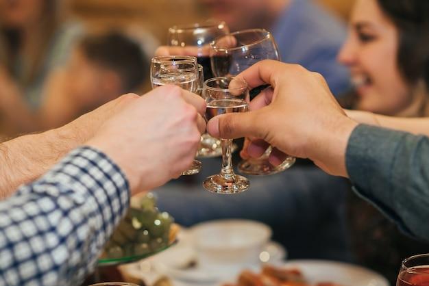 Mãos de um grupo de amigos tilintar de copos de bebida alcoólica e brindar e felicitar