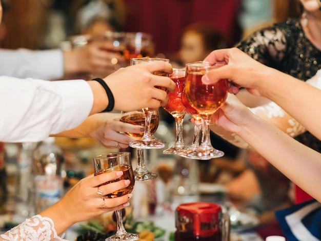 Mãos de um grupo de pessoas tilintar e brindar a copos de vinho tinto em uma festa festiva em um restaurante