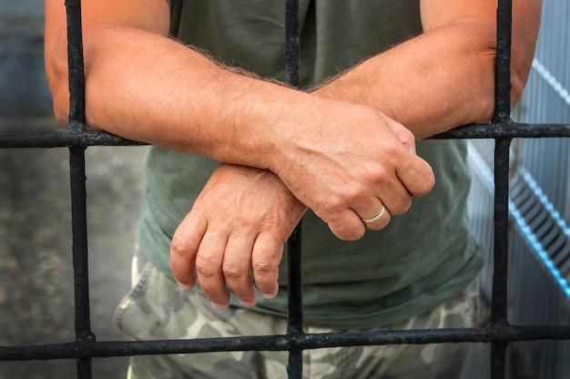 Mãos, de, um, homem, atrás de, barras, prisões