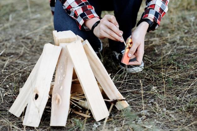 Mãos de um homem com fósforos curtos acendem uma fogueira com fósforos na natureza