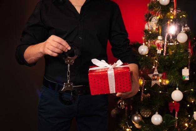 Mãos de um homem com uma caixa de presente e algemas de bdsm na árvore de natal. presente erótico para o ano novo para jogos sexuais