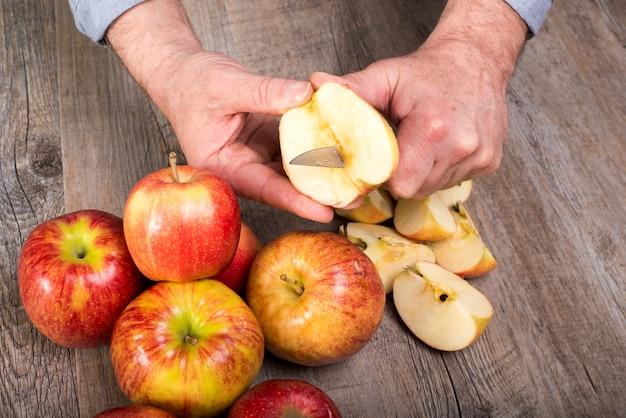 Mãos de um homem cortando uma maçã