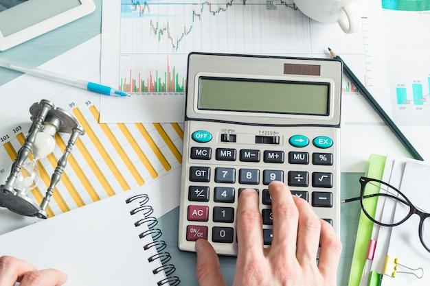 Mãos de um homem de negócio que prepara um relatório financeiro e que trabalha em uma calculadora.