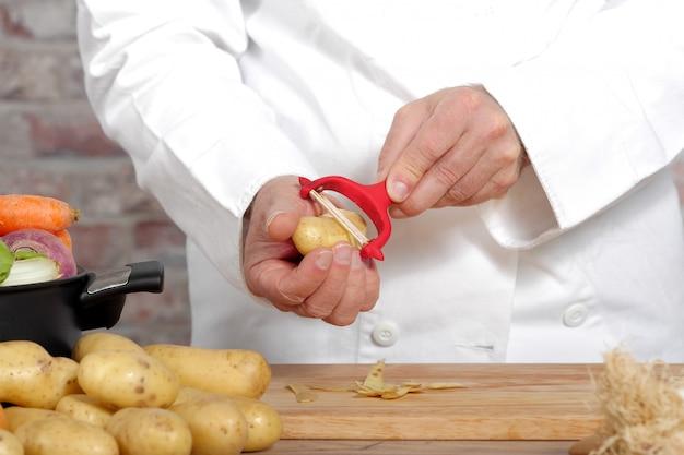 Mãos de um homem descascar batata com descascador
