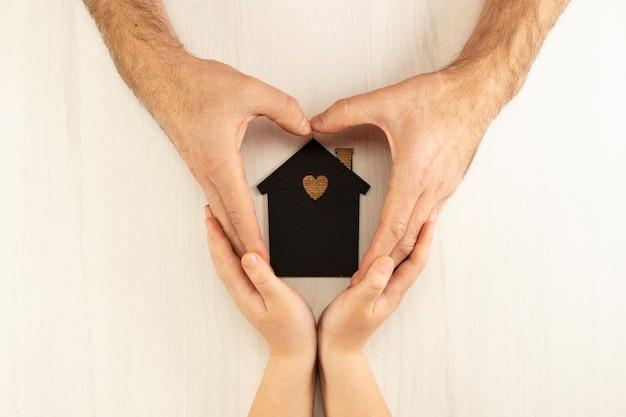 Mãos de um homem e uma criança cercam a maquete de uma casa escura sobre um fundo cinza