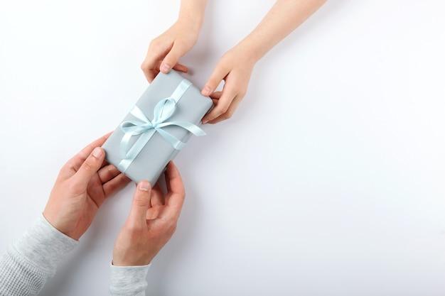Mãos de um homem e uma criança segurando uma vista de cima de um presente