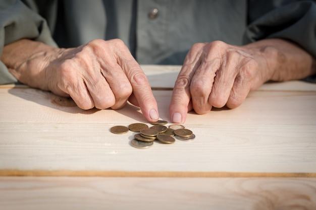 Mãos de um homem idoso segurando moedas. o conceito de falta de dinheiro, dos pobres, da pequena pensão dos idosos. imagem.