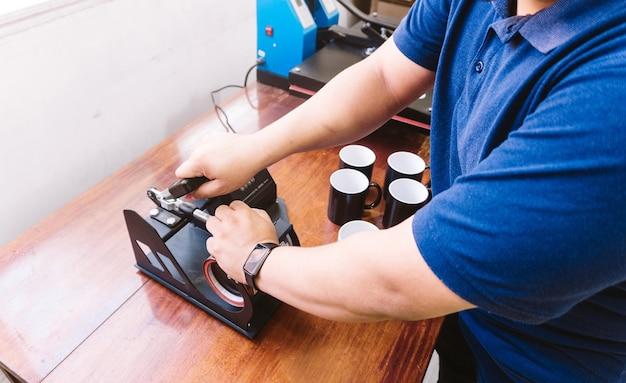 Mãos de um homem irreconhecível segurando uma máquina de sublimação em uma caneca