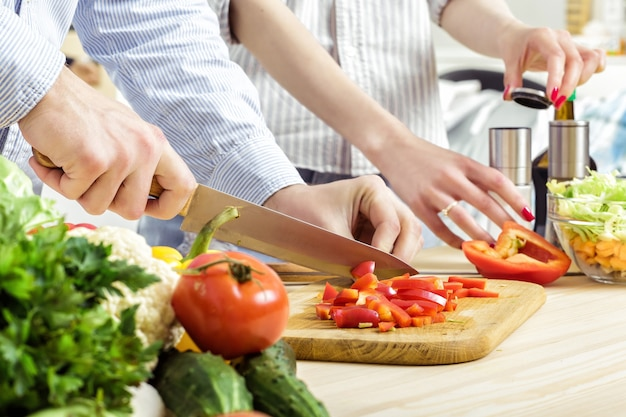 Mãos de um homem picado pimentão vermelho para salada em uma placa. casal cortando vegetais na cozinha
