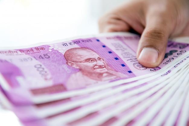 Mãos de um homem segurando dinheiro, moeda da rúpia indiana
