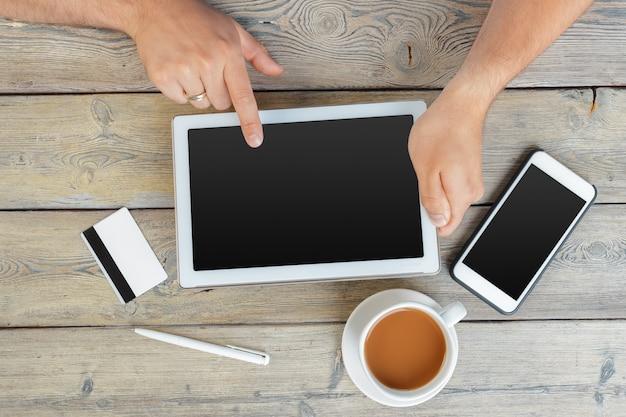 Mãos, de, um, homem, segurando, dispositivo tabuleta, sobre, um, madeira, espaço de trabalho, tabela