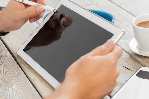 Mãos, de, um, homem, segurando, em branco, tabuleta, dispositivo, sobre, um, madeira, workspace, tabela