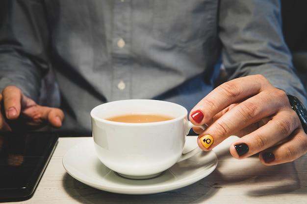 Mãos de um homem segurando uma xícara de chá e usa um smartphone na mesa de madeira. um homem com unhas pintadas. desenho de unhas masculinas. manicure dos homens.