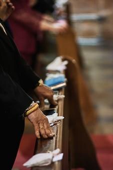 Mãos de um homem sênior com anel no dedo que fica em uma igreja.