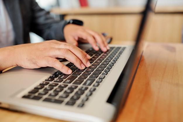 Mãos de um homem sentado na mesa do escritório e programando no laptop ou trabalhando no relatório mensal