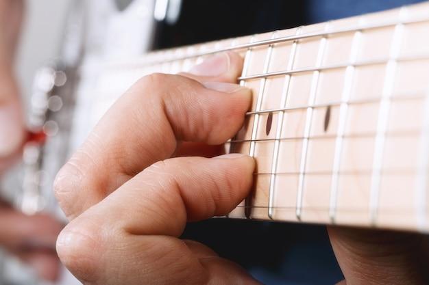 Mãos de um homem tocando guitarra elétrica com a palheta vermelha closeup