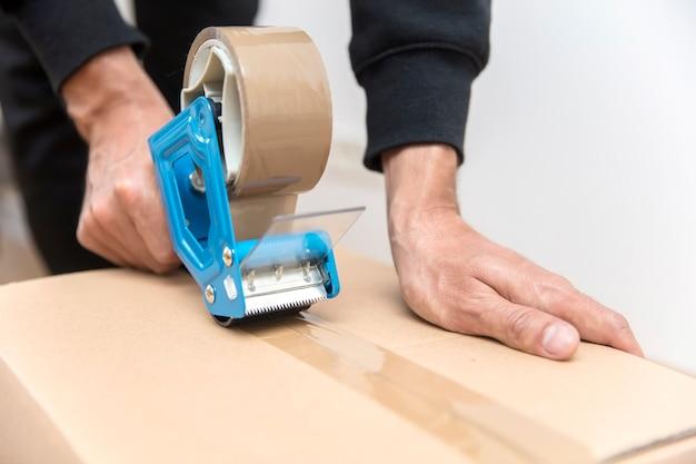 Mãos de um homem usando um dispensador de fita para selar uma caixa de transporte