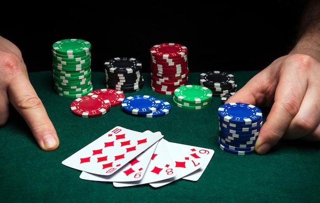 Mãos de um jogador, closeup e fichas na mesa verde em um clube de pôquer