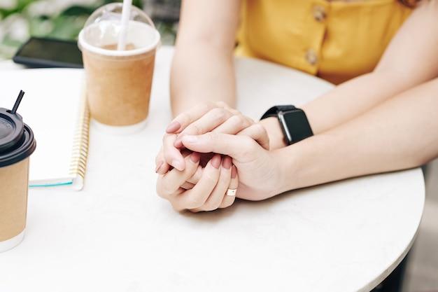Mãos de um jovem casal apaixonado, sentado à mesa em um café ao ar livre e tocando as mãos