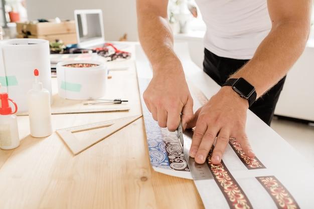 Mãos de um jovem criativo com smartwatch cortando uma das amostras de decoração com uma faca de aço inoxidável enquanto se inclina sobre a mesa de madeira