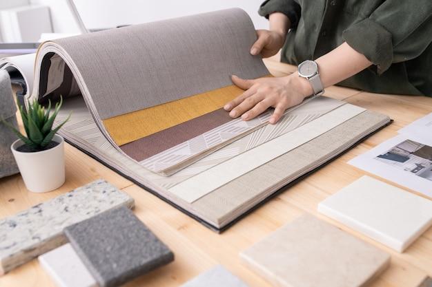 Mãos de um jovem designer de interiores em pé ao lado da mesa e escolhendo papéis de parede para um novo pedido entre as amostras de painel