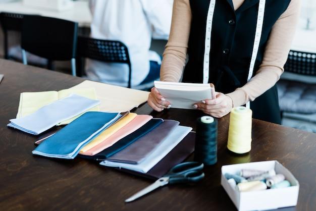 Mãos de um jovem designer elegante com o bloco de notas sobre a mesa trabalhando com amostras de têxteis para a nova coleção de moda na oficina