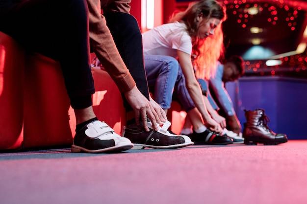 Mãos de um jovem em trajes casuais calçando sapatos para jogar boliche enquanto está sentado no banco na parede de seus amigos
