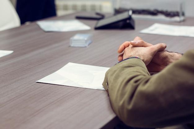 Mãos de um jovem em uma reunião de escritório com os parceiros de negócios