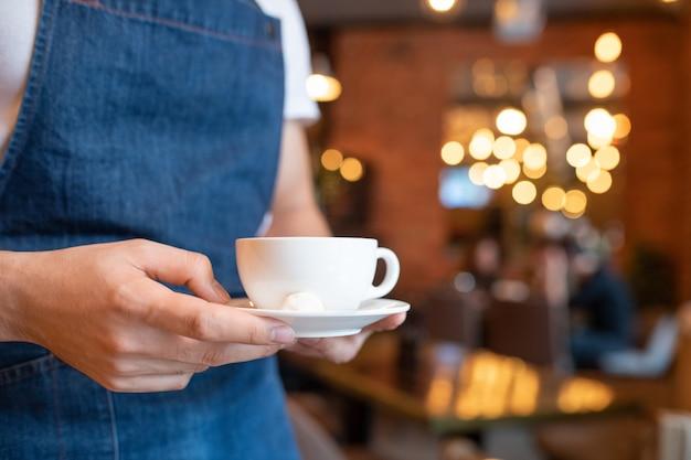 Mãos de um jovem garçom com avental azul carregando uma xícara de café ou chá em um pires de porcelana branca para um dos clientes de um café ou restaurante