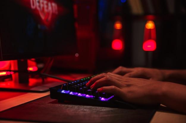 Mãos de um jovem jogador perdendo ao jogar videogame no computador em um quarto escuro, usando o teclado colorido com iluminação
