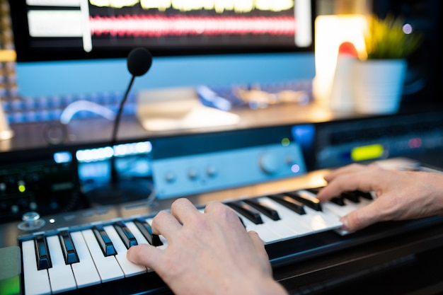 Mãos de um jovem músico pressionando as teclas do teclado de piano na frente do microfone e do monitor do computador enquanto grava música