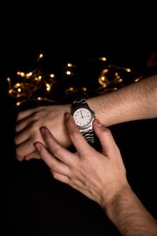 Mãos de um jovem olhando para um relógio prestes a marcar o primeiro segundo do novo ano de 2019