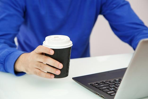 Mãos de um jovem segurando café e imprimir em um laptop