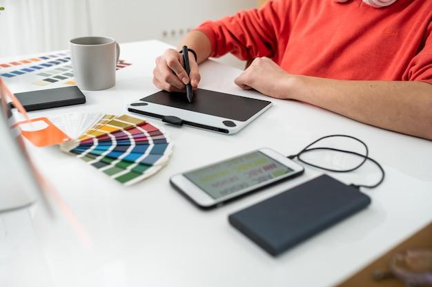 Mãos de um jovem web designer freelance segurando uma caneta sobre a tela do tablet gráfico enquanto retoca as fotos na mesa