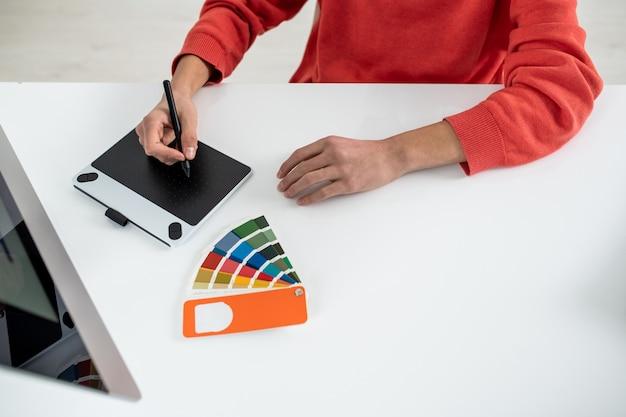 Mãos de um jovem web designer segurando uma caneta sobre a mesa gráfica enquanto está sentado na mesa em frente à tela do computador