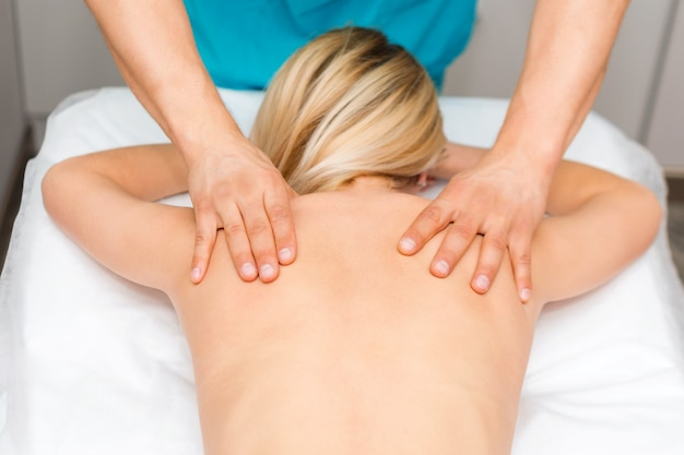 Mãos de um massagista fazendo massagem nas costas de uma mulher. jovem mulher que tem o procedimento de esculpir o corpo. ajuste nas costas de quiropraxia. osteopatia, medicina alternativa, conceito de alívio de dor.