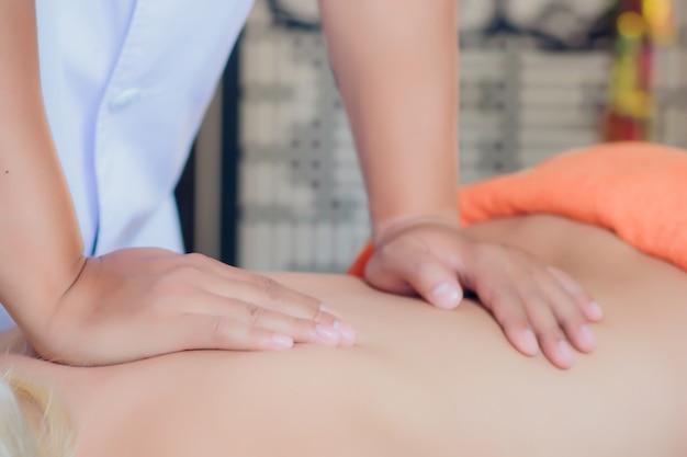 Mãos de um massagista massageando as costas de uma jovem mulher