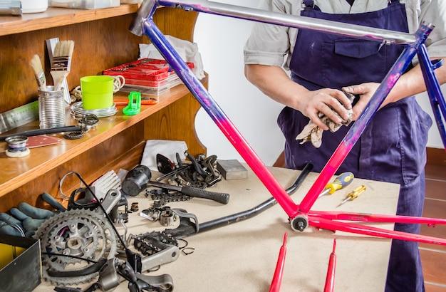 Mãos de um mecânico de bicicleta real limpando uma bicicleta com estrutura danificada em uma oficina