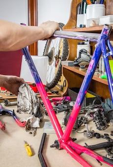 Mãos de um mecânico de bicicletas de verdade limpando uma bicicleta com estrutura danificada em uma oficina