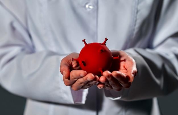 Mãos de um médico segurando modelo de célula de coronavírus