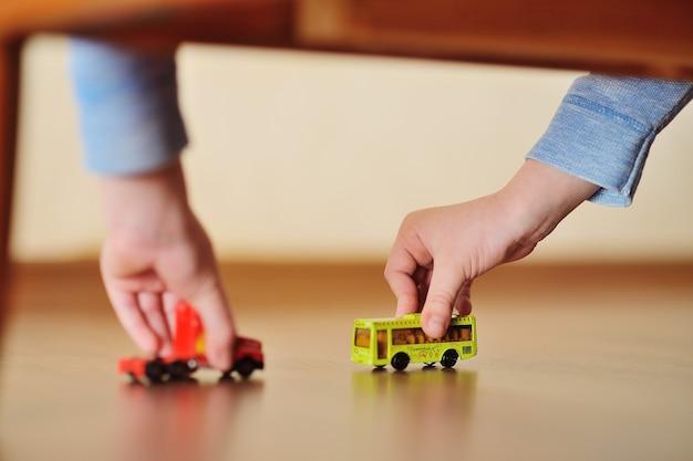 Mãos de um menino criança com um carrinho de brinquedo e uma vista de ônibus debaixo da cama.