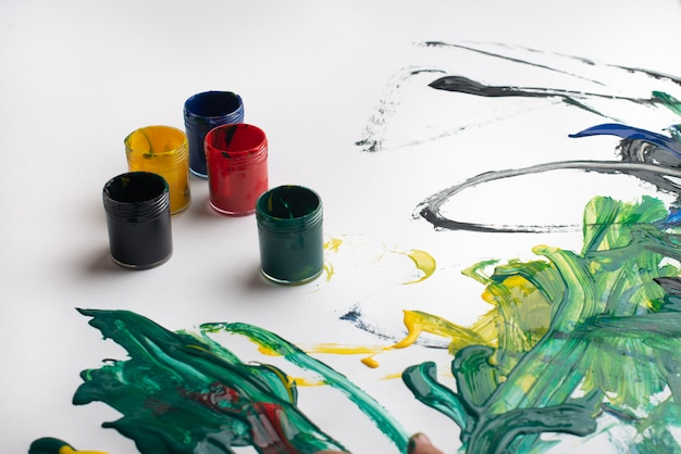 Mãos de um menino pintando com aquarelas na folha de papel branco. garotinho com um pincel e tintas.
