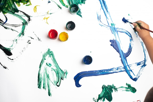 Mãos de um menino pintando com aquarelas na folha de papel branco.