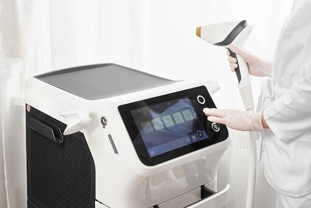 Mãos de um mestre com modernos equipamentos para depilação a laser e depilação em salão de beleza. salão de beleza e cosmetologia