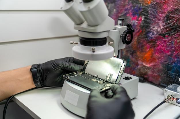 Mãos de um mestre examinando um smartphone desmontado através de um microscópio