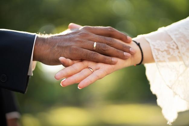 Mãos de um noivo de pele escura e noiva de pele clara com anéis se tocam suavemente perto acima vista
