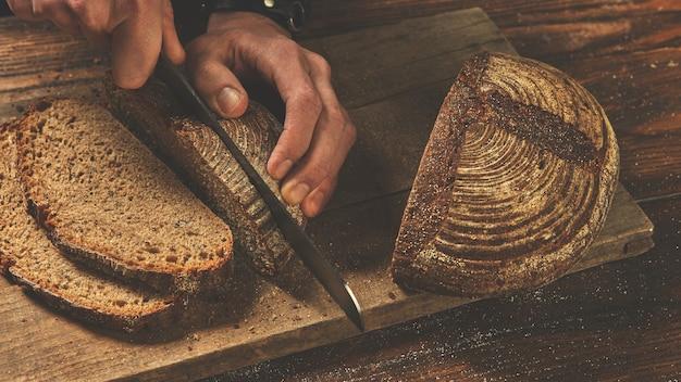 Mãos de um padeiro cortam um pão escuro rural em uma placa de madeira
